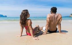 Par på strandsommarsemester, ungdomarsom sitter på sand, hav för mankvinnahav Royaltyfria Bilder