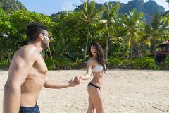 Par på strandsommarsemestern, ungdomarförälskat gå, semesterort för hav för hav för händer för mankvinnainnehav Arkivfoton