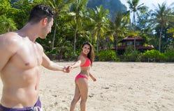 Par på strandsommarsemestern, ungdomarförälskat gå, semesterort för hav för hav för händer för mankvinnainnehav Arkivfoto