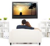 Par på hållande ögonen på TV för soffa Arkivbilder