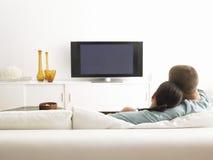 Par på Sofa Watching TV Arkivbilder