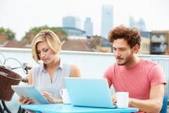 Par på takterrass genom att använda bärbara datorn och den Digital minnestavlan Arkivbild