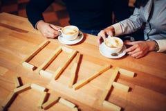 Par ręki kawa na drewnianym stole Zdjęcia Stock