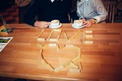 Par ręki kawa na drewnianym stole Zdjęcia Royalty Free