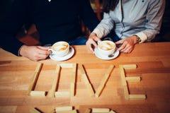 Par ręki kawa na drewnianym stole Obraz Stock