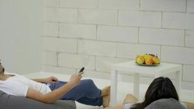 Par returnerar hållande ögonen på television i stol för att hänga löst lager videofilmer