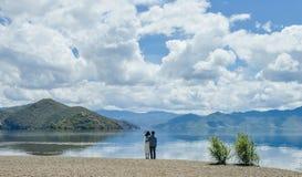 Par rymmer tillsammans att se bort på stranden Arkivbilder
