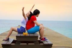 Par sitter tillsammans på tabellen nära stranden royaltyfri foto