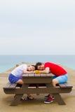 Par sitter tillsammans på tabellen nära stranden royaltyfri fotografi