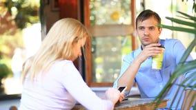 Par som är förälskade i ett utomhus- kafé Man och härlig kvinna på ett datum Alla ser hans mobiltelefon stock video