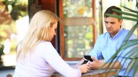 Par som är förälskade i ett utomhus- kafé Man och härlig kvinna på ett datum Alla ser hans mobiltelefon lager videofilmer