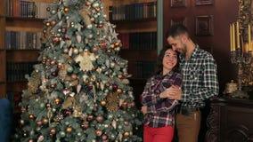 Par som är förälskade nära den dekorerade julgranen lager videofilmer