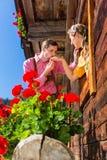Par som är förälskade på bergkojafönstret Royaltyfri Fotografi