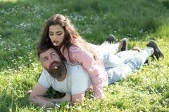 Par som är förälskade på soligt utomhus- Kvinna som ligger på man med blommor i munnar Par kopplar av på grönt gräs carefree tid Arkivfoto