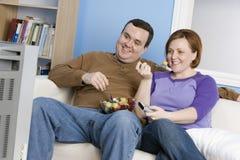 Par som äter frukter, medan hålla ögonen på television Arkivfoton
