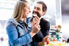 Par som äter fruktglasscoupen med garnering i glasskafé Arkivfoton