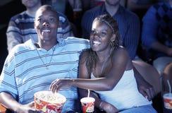 Par som äter popcorn, medan hålla ögonen på film i teater Arkivfoto