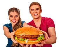 Par som äter snabbmat Man- och kvinnafesthamburgare Arkivfoto