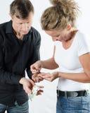 Par som argumenterar om pengar på hennes hand Arkivfoto