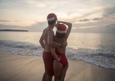 Par som bär den santa hatten på stranden Arkivbild