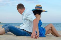 Par som baksidt sitter till backen på strand Arkivbilder
