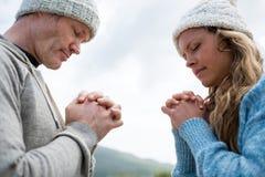 Par som ber med knäppte fast händer Arkivfoton