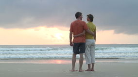 Par som beskådar soluppgången på en strand stock video