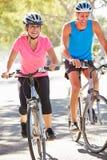Par som cyklar på den förorts- gatan Royaltyfri Fotografi