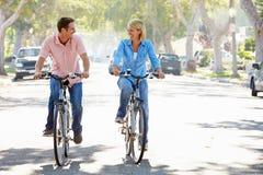 Par som cyklar på den förorts- gatan Arkivfoto