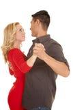 Par som dansar den röda klänningen, ser in i ögon Royaltyfri Bild
