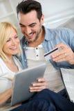 Par som direktanslutet hemifrån shoppar med minnestavlan Arkivbild