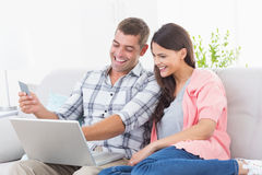 Par som direktanslutet shoppar till och med bärbara datorn genom att använda kreditkorten Royaltyfri Fotografi