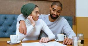 Par som diskuterar menykortet i kafét 4k lager videofilmer