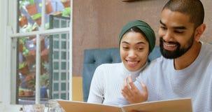 Par som diskuterar menykortet i kafét 4k arkivfilmer