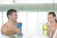 Par som dricker coctailen, genom simbassängen och att koppla av Arkivfoto