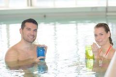 Par som dricker coctailen, i simbassäng och att koppla av Arkivbilder