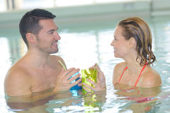 Par som dricker coctailen, i simbassäng och att koppla av Royaltyfria Bilder