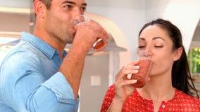 Par som dricker exponeringsglas av smoothien arkivfilmer
