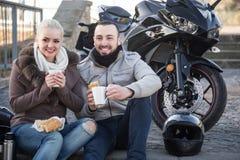 Par som dricker kaffe nära motorcykeln arkivfoton