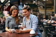 Par som dricker kaffe på datum i kafé fotografering för bildbyråer