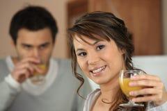 Par som dricker orange fruktsaft Royaltyfri Fotografi