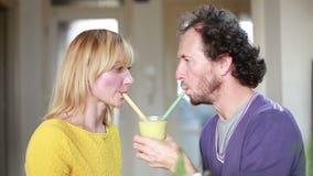 Par som dricker smoothien från samma dricka exponeringsglas arkivfilmer