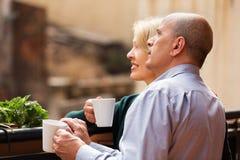 Par som dricker te på balkongen Arkivbilder