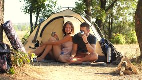 Par som dricker te på campingplatstältet arkivfilmer
