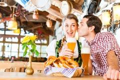 Par som dricker veteöl i bayersk restaurang Royaltyfria Bilder