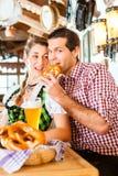 Par som dricker veteöl i bayersk restaurang Arkivfoto