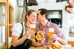 Par som dricker veteöl i bayersk restaurang Arkivfoton
