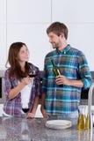 Par som dricker vin i köket Arkivfoton