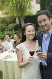 Par som dricker vin med vänner i bakgrunden Fotografering för Bildbyråer