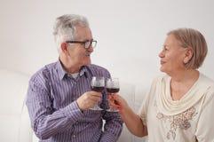 Par som dricker vin och rostar sig royaltyfri fotografi